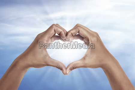 heart shaped hand with blue sky