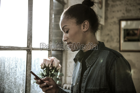young woman standing indoors by a