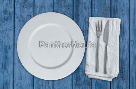empty plate with cutlery on blue