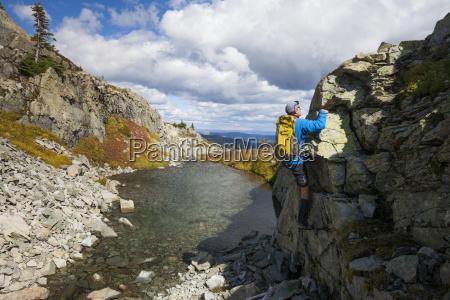 man climbing on rock by stream