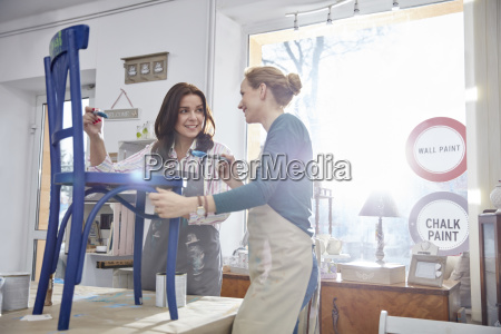 smiling female artists painting chair blue