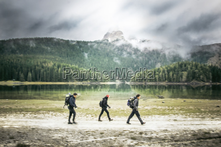 three hikers walking beside mountain lake