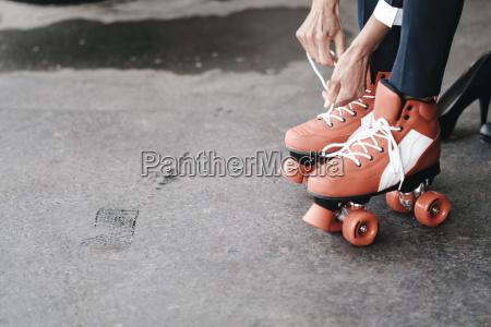 businesswoman tying her roller skates close