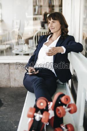 businesswoman wearing roller skates drinking coffee