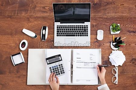 businessperson analyzing bill in office
