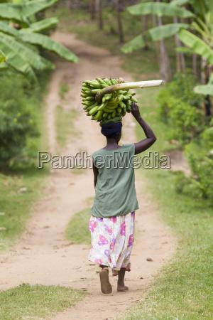 uma mulher atravessa um caminho carregando