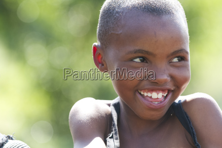 a young girl smiling and looking