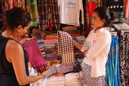 mulher comprando lencois no mercado de