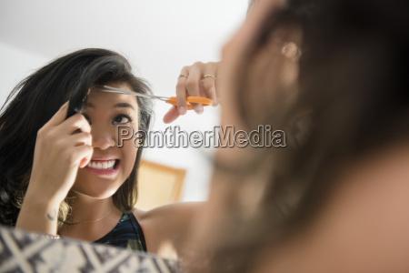 uncertain mixed race woman cutting bangs