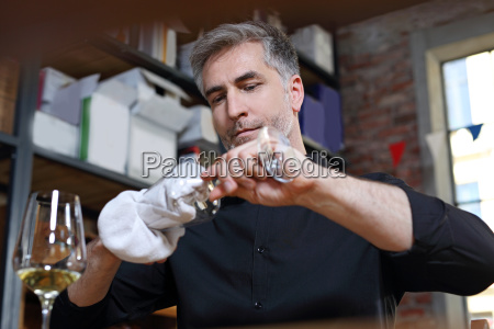the waiter polishes the glass