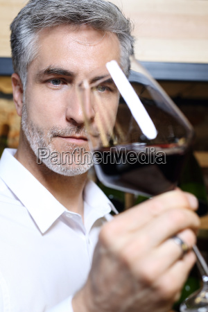 red wine man evaluates the color
