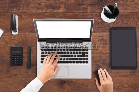 businessperson using laptop with blank white