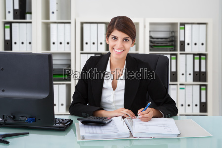 confident businesswoman using calculator at office