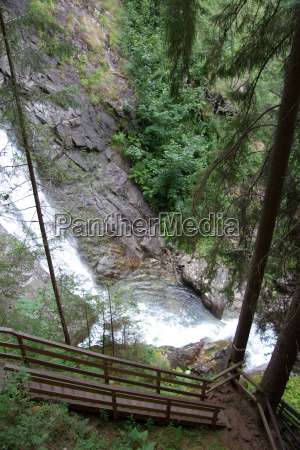 paved wooden walkway with waterfall in