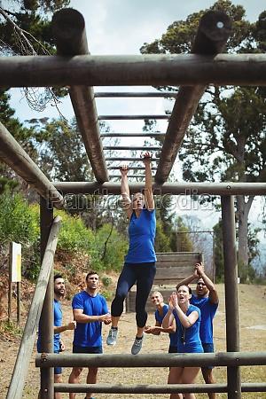 fit woman climbing monkey bars