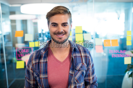 smiling man standing against sticky notes