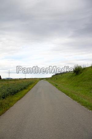 empty asphalt road between green boundaries