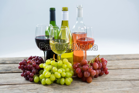 bunches of various grapes with wine