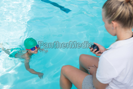 female trainer monitoring time of boy