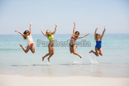 friends in bikinis jumping on shore