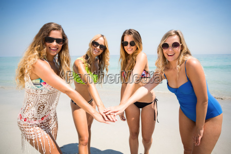 young friends in bikinis stacking hands