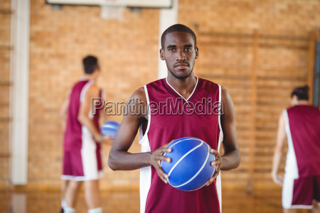 confident basketball player holding a