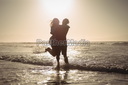 silhouette couple enjoying on shore at