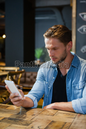 man using mobile phone while sitting