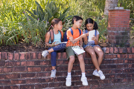 friends discussing over digital tablet at