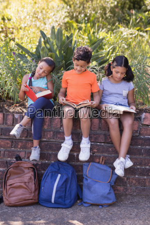 smiling friends reading books at natural