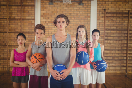 confident high school kids holding basketball