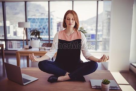 beautiful executive meditating on desk