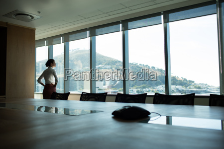 businesswoman looking through window in conference