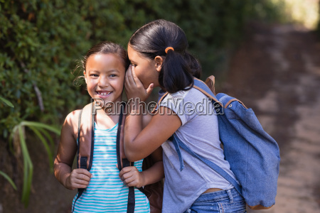 girl whispering to smiling friend natural