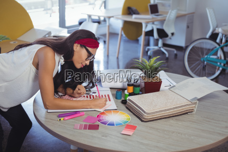businesswoman working while leaning on desk