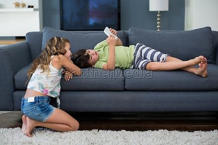 siblings using digital tablet in living