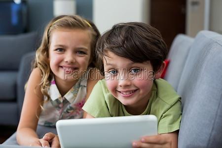 portrait of siblings using digital tablet
