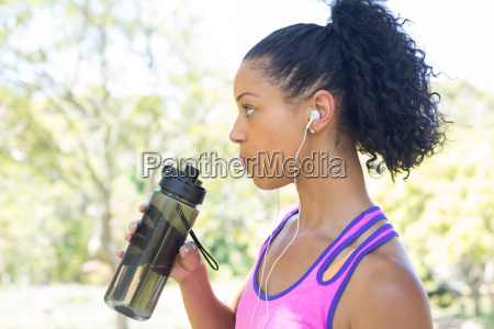 female jogger drinking water in the