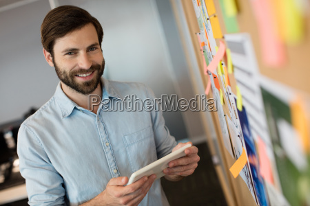 portrait of young businessman holding digital
