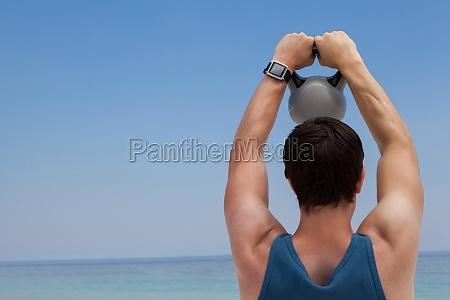 rear view of man lifting kettlebell