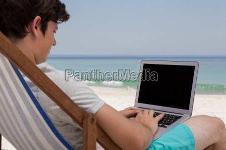 man using laptop at beach