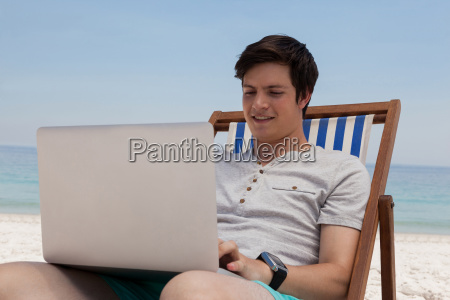 man sitting on sunlounger and using