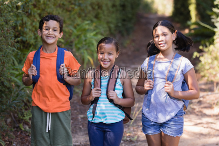 smiling friends carrying backpack at natural