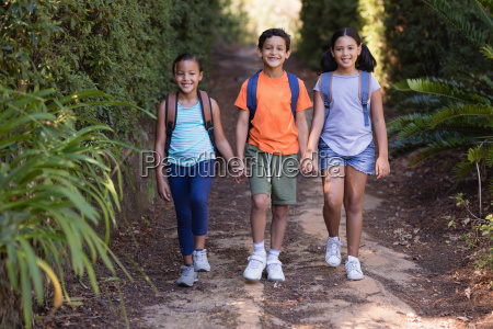 portrait of smiling friends carrying backpack