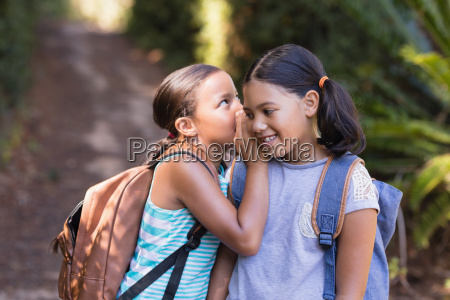 girl whispering to friend at natural
