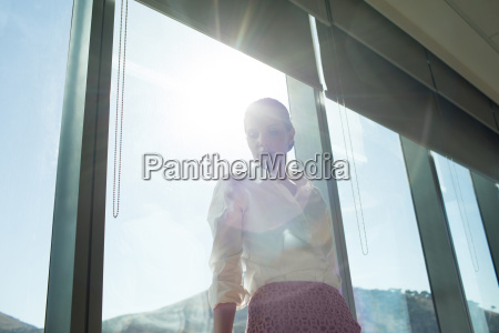 businesswoman standing by brightly lit window