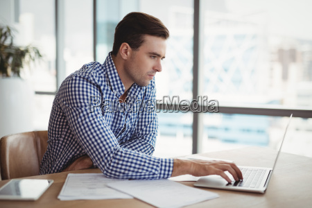 attentive executive using laptop at desk