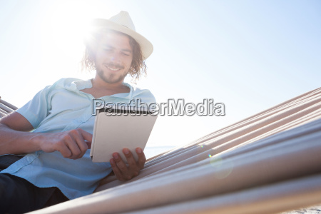 man relaxing on hammock and using