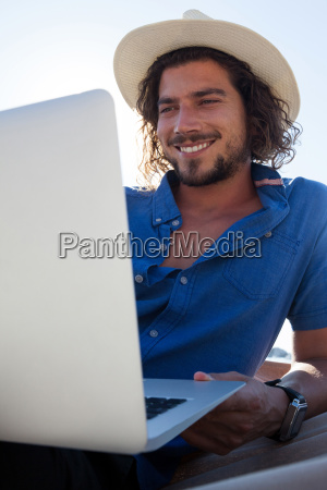 happy man using laptop while relaxing