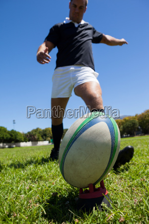 player kicking rugby ball on grassy